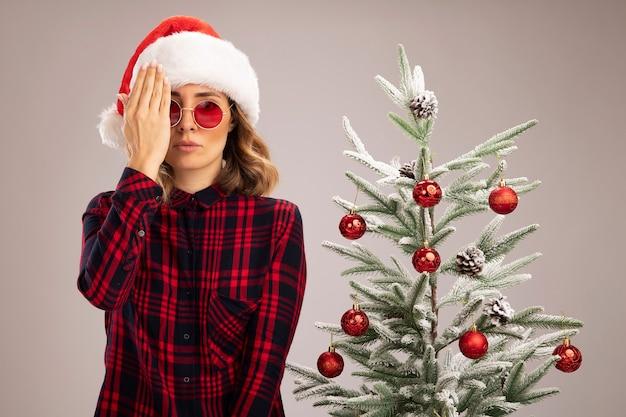 Betrachtet man die kamera junges schönes mädchen, das in der nähe des weihnachtsbaums steht und einen weihnachtshut mit brille trägt, bedeckte das auge mit der hand isoliert auf weißem hintergrund