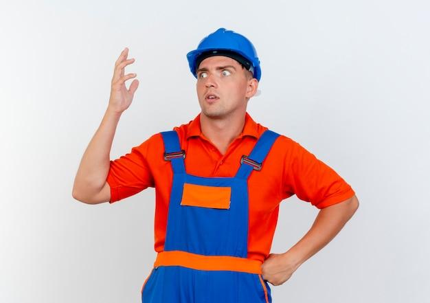 Betrachtet man die seite, beeindruckte der junge männliche baumeister, der uniform und schutzhelm trägt und die hand anhebt, die die andere hand auf die hüfte legt