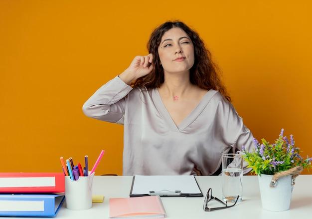 Betrachtet man die seite denkende junge hübsche büroangestellte, die am schreibtisch sitzt?