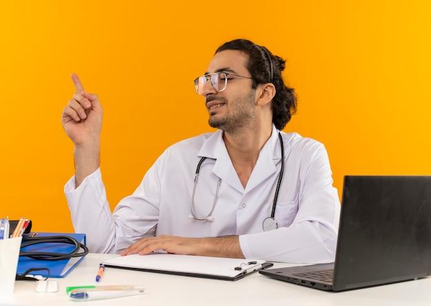 Betrachtet man einen lächelnden jungen männlichen arzt mit medizinischer brille, der ein medizinisches gewand mit stethoskop trägt, das am schreibtisch sitzt?