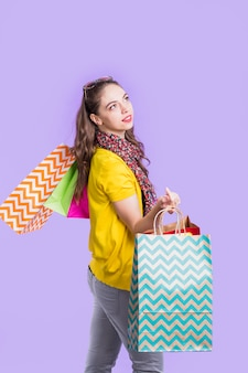Betrachtung der frau, die einkaufstasche gegen purpurroten hintergrund hält