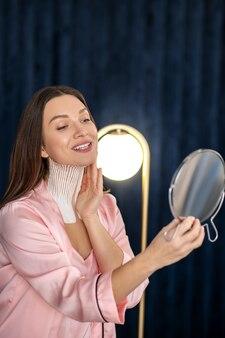 Betrachtung. junge frau in rosa dessous und mit bändern an ihrem hals, der in den spiegel schaut und lächelt