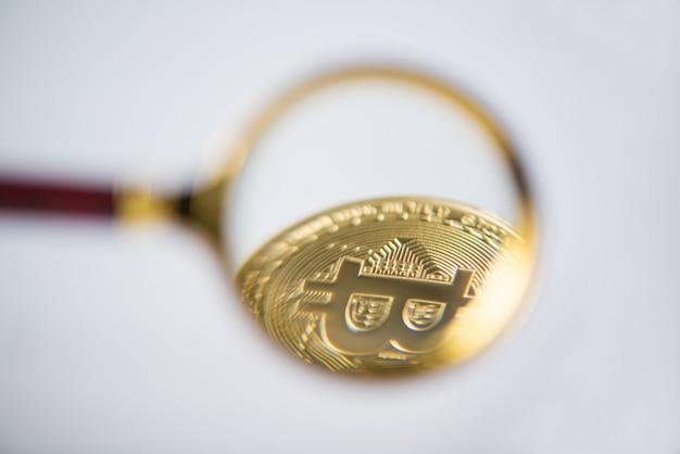Betrachtung und erhöhung von bitcoin durch eine lupe. elektronisches geld