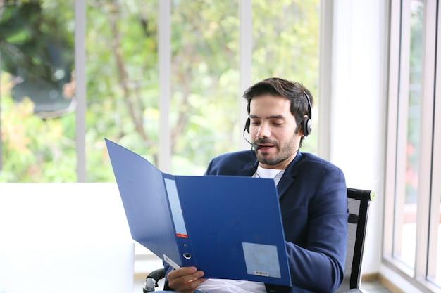 Betreiber des technischen supports mit dem kopfhörer, der am laptop und am computer arbeitet