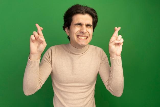 Betroffen mit geschlossenen augen junger hübscher kerl, der finger auf grüner wand kreuzt