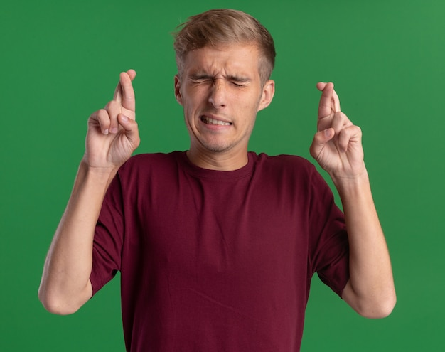 Betroffen mit geschlossenen augen junger hübscher kerl, der rotes hemd trägt, das finger kreuzt, die auf grüner wand lokalisiert werden