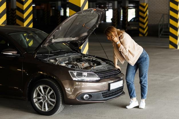 Betroffene fahrerin in jeans und windjacke, die auf dem parkplatz um hilfe ruft, um bei der panne des autos zu helfen