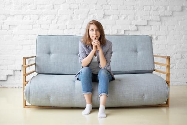 Betroffene fokussierte junge frau in jeans und weißen socken, die auf grauer couch gegen weißen backsteinmauerhintergrund sitzen, konzentrierten nachdenklichen blick haben, lippen spitzen, über hausrenovierungsideen nachdenken