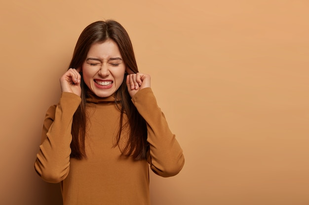 Betroffene frustrierte frau steckt die ohren zu, beißt die zähne zusammen, hört störende geräusche, vermeidet unangenehme geräusche, trägt braune kleidung, kann nicht mehr hören