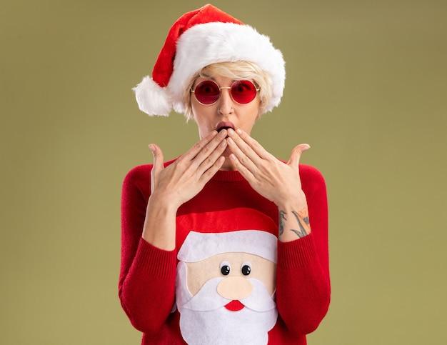 Betroffene junge blonde frau, die weihnachtsmütze und weihnachtsmannpullover des weihnachtsmannes mit brille trägt, die kamera betrachtet, die hände auf mund lokalisiert auf olivgrünem hintergrund hält