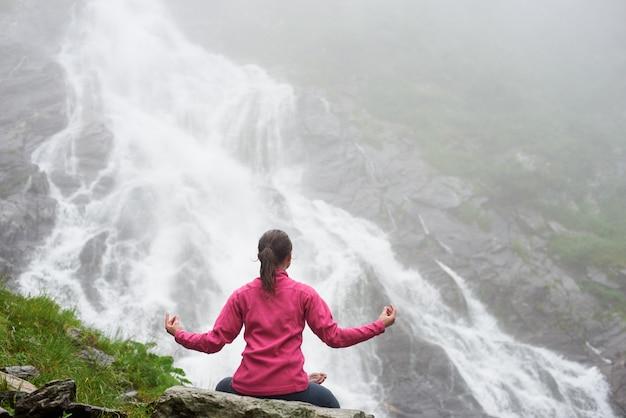 Betroffene junge frau meditiert über felsen und praktiziert yoga vor einem spektakulären wasserfall