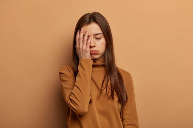 Betroffene müdigkeit frau bedeckt gesicht mit handfläche, fühlt sich gelangweilt und müde, will schlaf nach der ganzen nacht prüfungsvorbereitung, braucht ruhe oder unterstützung