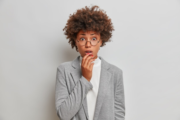 Betroffene nervöse unternehmerin hält in schwierigen momenten den atem an, hält die hand auf den lippen und trägt formelle kleidung