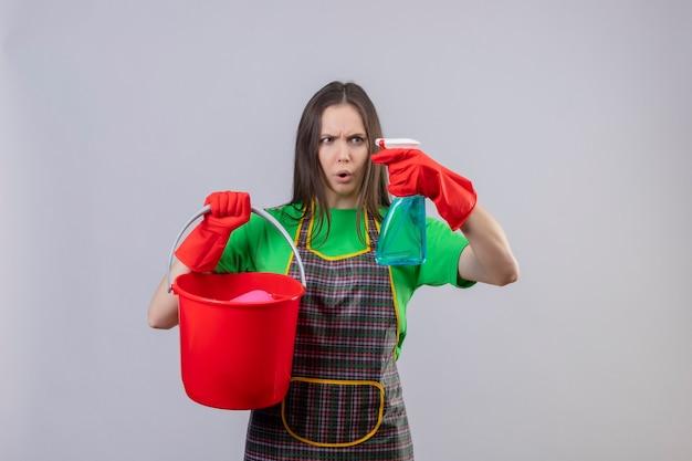 Betroffene reinigende junge frau, die uniform in roten handschuhen hält, die eimer halten, der reinigungsspray auf ihrer hand auf isolierter weißer wand sucht