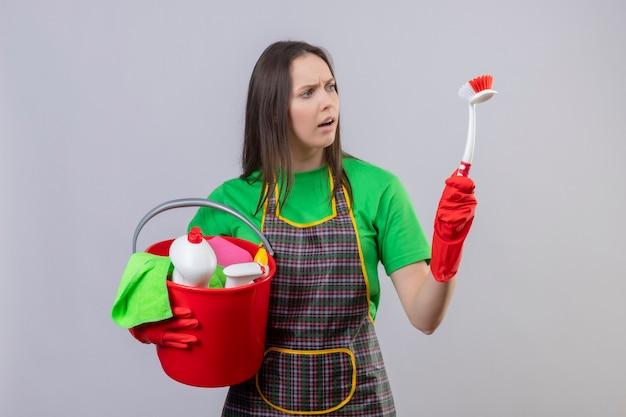 Betroffene reinigende junge frau, die uniform in roten handschuhen hält, die reinigungswerkzeuge halten, die reinigungsbürste auf ihrer hand auf isolierter weißer wand suchen