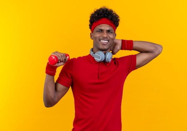 Betroffener junger afroamerikanischer sportlicher mann, der stirnband und armband mit kopfhörern am hals hält hantel hält und hand hinter kopf lokalisiert auf gelbe wand legt