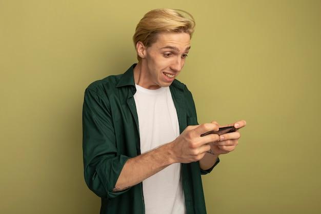 Betroffener junger blonder kerl, der grünes t-shirt trägt, das am telefon spielt
