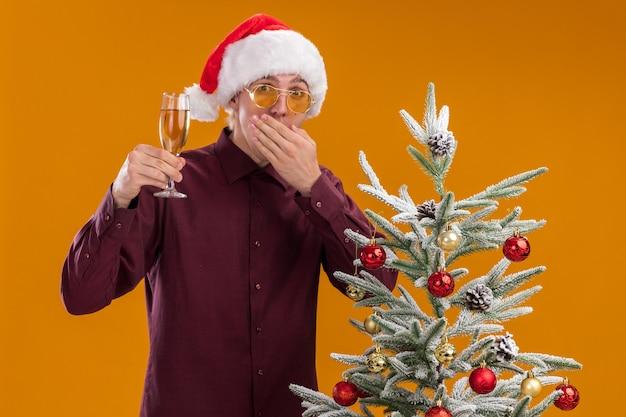 Betroffener junger blonder mann, der weihnachtsmütze und gläser trägt, die nahe geschmücktem weihnachtsbaum auf orange hintergrund stehen