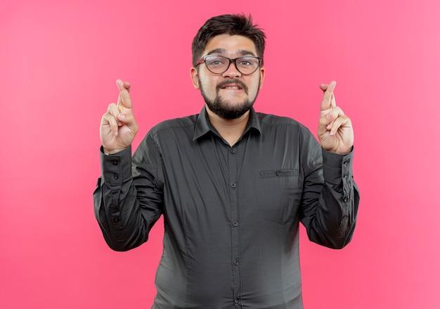 Betroffener junger geschäftsmann, der brillen trägt, die finger auf rosa wand lokalisieren
