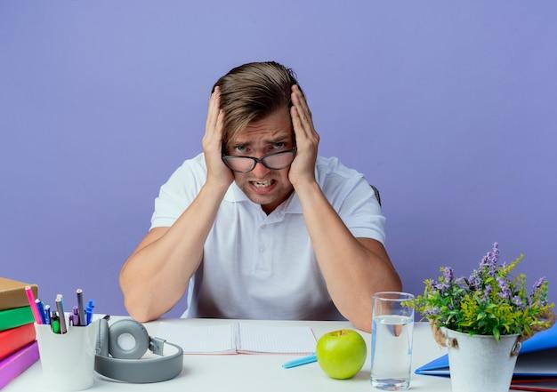Betroffener junger hübscher männlicher student, der am schreibtisch mit schulwerkzeugen sitzt, die brille tragen und ohren schließen, die auf blauem hintergrund lokalisiert werden