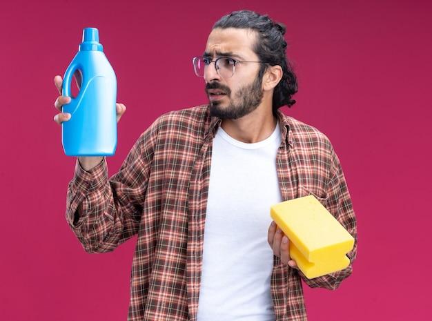 Betroffener junger hübscher reinigungsmann, der t-shirt trägt, das schwamm hält und reinigungsmittel in seiner hand lokalisiert auf rosa wand betrachtet