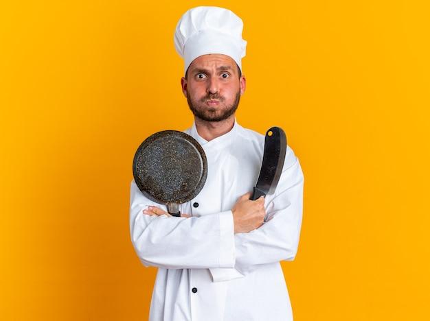 Betroffener junger kaukasischer männlicher koch in der kochuniform und in der kappe, die mit geschlossener haltung stehen, die hackbeil und bratpfanne mit aufgeblähten wangen auf orange wand mit kopienraum hält