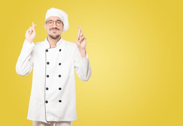 Betroffener junger koch, der eine geste mit gekreuzten fingern macht