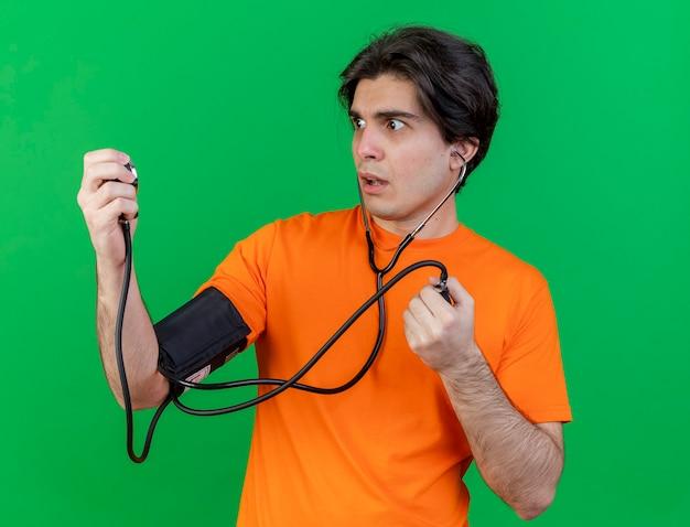 Betroffener junger kranker mann, der seinen eigenen druck mit einem auf grün isolierten blutdruckmessgerät misst