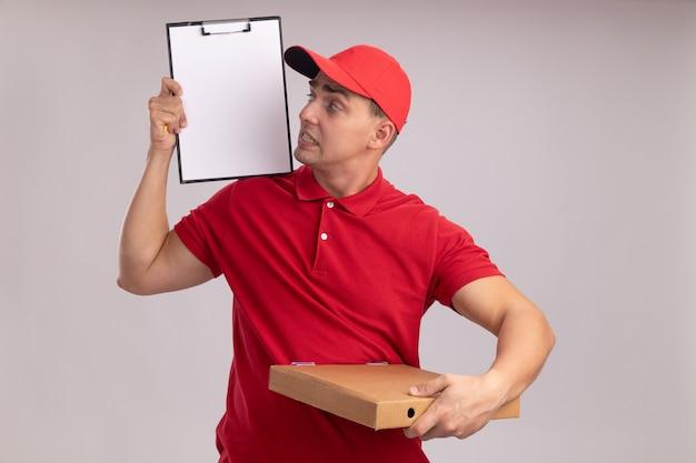 Betroffener junger lieferbote, der uniform mit kappe hält, die pizzaschachtel hält und klemmbrett in seiner hand lokalisiert auf weißer wand betrachtet