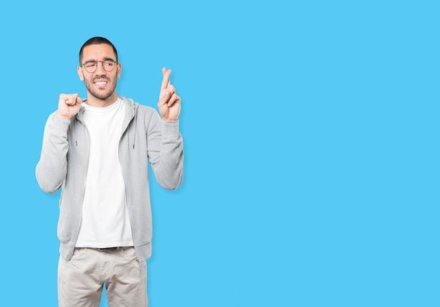 Betroffener junger mann, der eine geste mit gekreuzten fingern macht