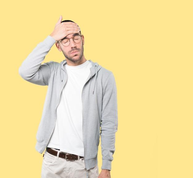 Betroffener junger mann mit einer geste des schmerzes
