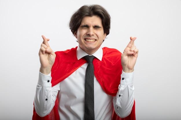 Betroffener junger superheld mit geschlossenen augen, die krawattenkreuzfinger lokalisiert auf weiß tragen