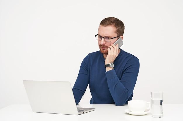 Betroffener junger unrasierter blonder geschäftsmann in brille, der mit seinem smartphone anruft, während er über weißem hintergrund in freizeitkleidung arbeitet