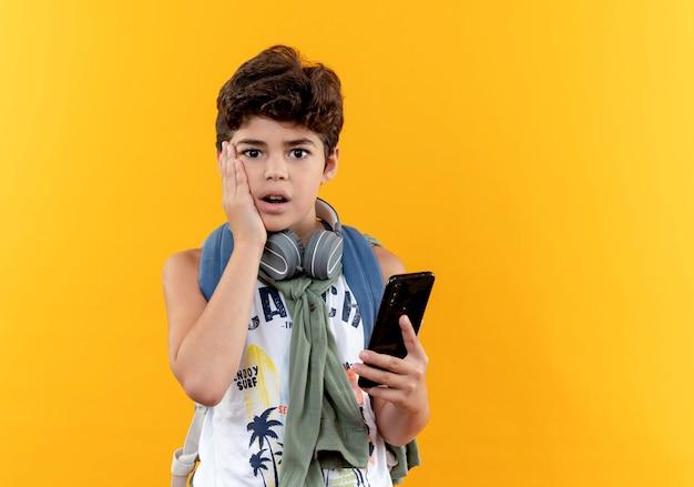 Betroffener kleiner schuljunge, der rückentasche und kopfhörer trägt telefon hält und hand auf wange lokalisiert auf gelbem hintergrund legt