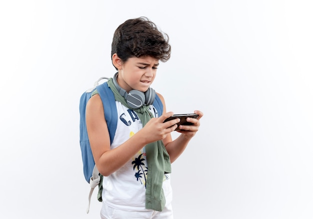 Betroffener kleiner schuljunge mit rucksack und kopfhörern am telefon