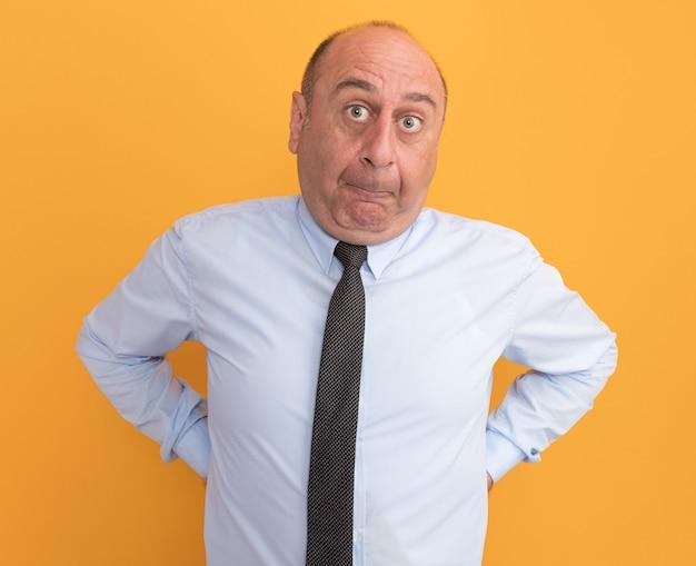 Betroffener mann mittleren alters, der weißes t-shirt mit krawatte trägt, die hände auf taille setzt, die auf orange wand lokalisiert werden