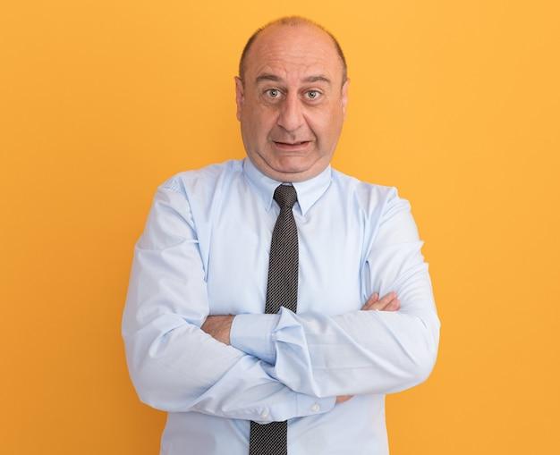 Betroffener mann mittleren alters, der weißes t-shirt mit krawattenkreuzungshänden trägt, die auf orange wand isoliert werden