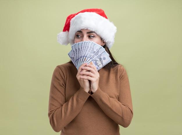 Betroffenes betrachten des jungen schönen mädchens der seite, das weihnachtshut bedeckte gesicht mit bargeld lokalisiert auf olivgrünem hintergrund trägt