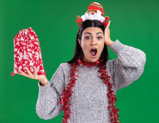 Betroffenes junges kaukasisches mädchen, das weihnachtsmann-stirnband und lametta-girlande um den hals hält, der weihnachtsgeschenk-sack betrachtet, der kamera betrachtet, die hand auf kopf lokalisiert auf grünem hintergrund hält