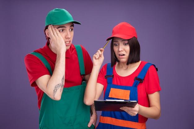 Betroffenes junges paar in bauarbeiteruniform und mützenmädchen, das bleistift und zwischenablage hält, die den kopf mit bleistift berühren, der den zwischenablage-kerl betrachtet, der hand auf gesicht hält, das seite betrachtet