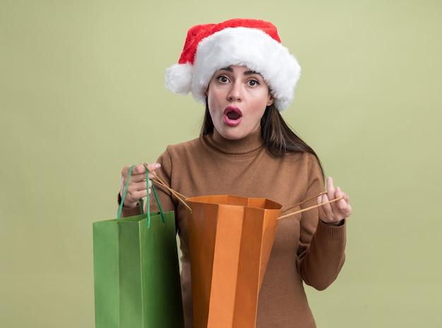 Betroffenes junges schönes mädchen, das weihnachtshut hält geschenktüte lokalisiert auf olivgrünem hintergrund trägt