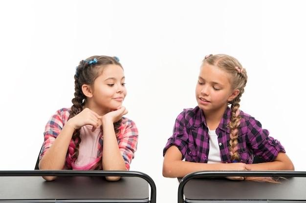 Betrug bei der prüfung. kleine schulkinder, die die prüfung getrennt auf weiß bestehen. kleines mädchen, das während der prüfung ihren klassenkameraden anguckt. ihre erste prüfung.