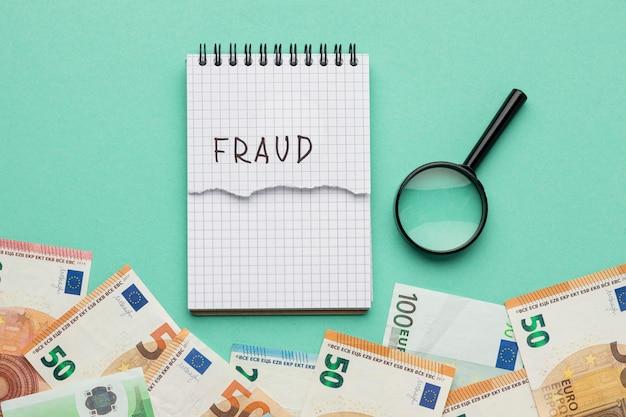 Betrugswort auf notizblock mit banknoten geschrieben