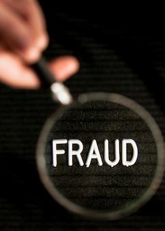 Betrugswort in einer lupe und unscharfer effekt