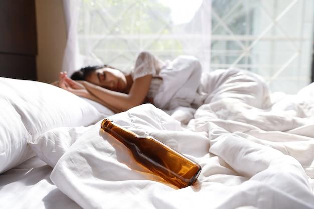 Betrunkene asiatische frau bewusstlos im bett nach zu viel alkohol trinken