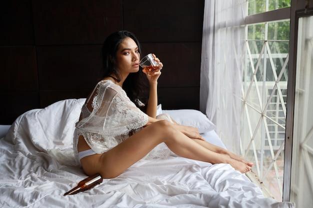 Betrunkene asiatische frau der seitenansicht in der weißen wäsche, flasche alkoholalkohol beim sitzen trinkend und halten auf bett im schlafzimmer