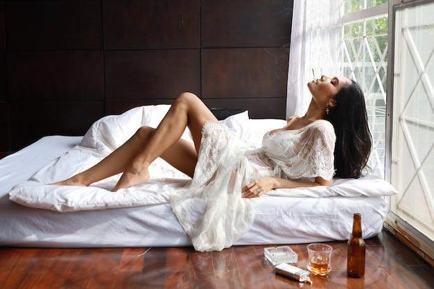 Betrunkene asiatische frau der seitenansicht in der weißen wäsche, trinkend und rauchen beim halten der flasche alkoholalkohols und lügens auf bett im schlafzimmer