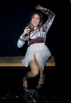 Betrunkene frau, die auf bank mit champagnerglas sitzt