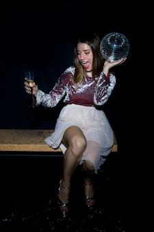 Betrunkene frau, die auf bank mit discokugel sitzt