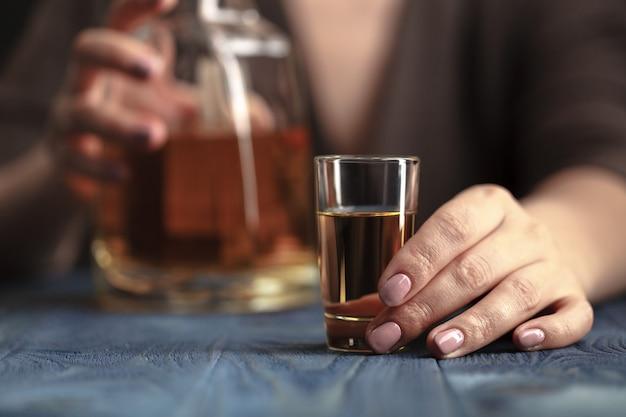 Betrunkene frau, die ein alkoholisches getränk, konzentriert auf das getränk hält